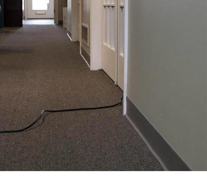 carpet pulled up in a hallway because of damage and a SERVPRO armorer drying the floor
