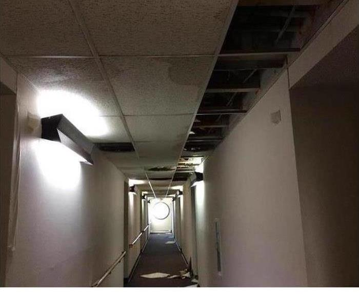 Hallway of a building with broken ceiling and fire damage