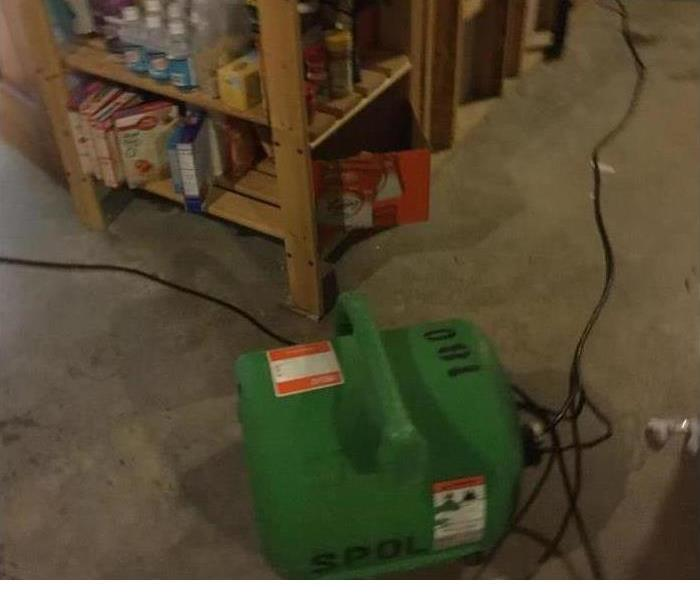 water damage being mitigated with a green SERVPRO dehumidifier