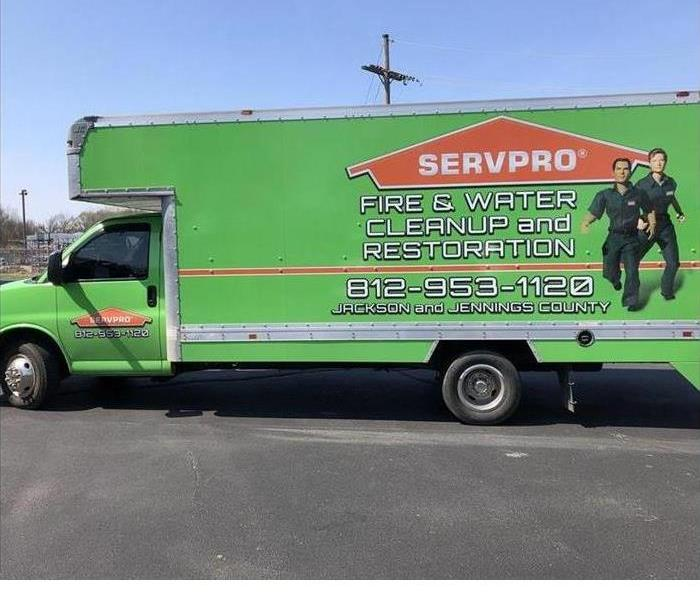 a green SERVPRO truck outside on a sunny day